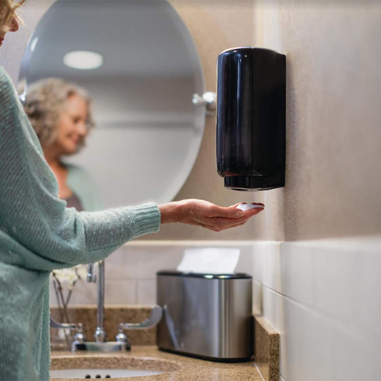 Woman with Tork touch free soap dispenser